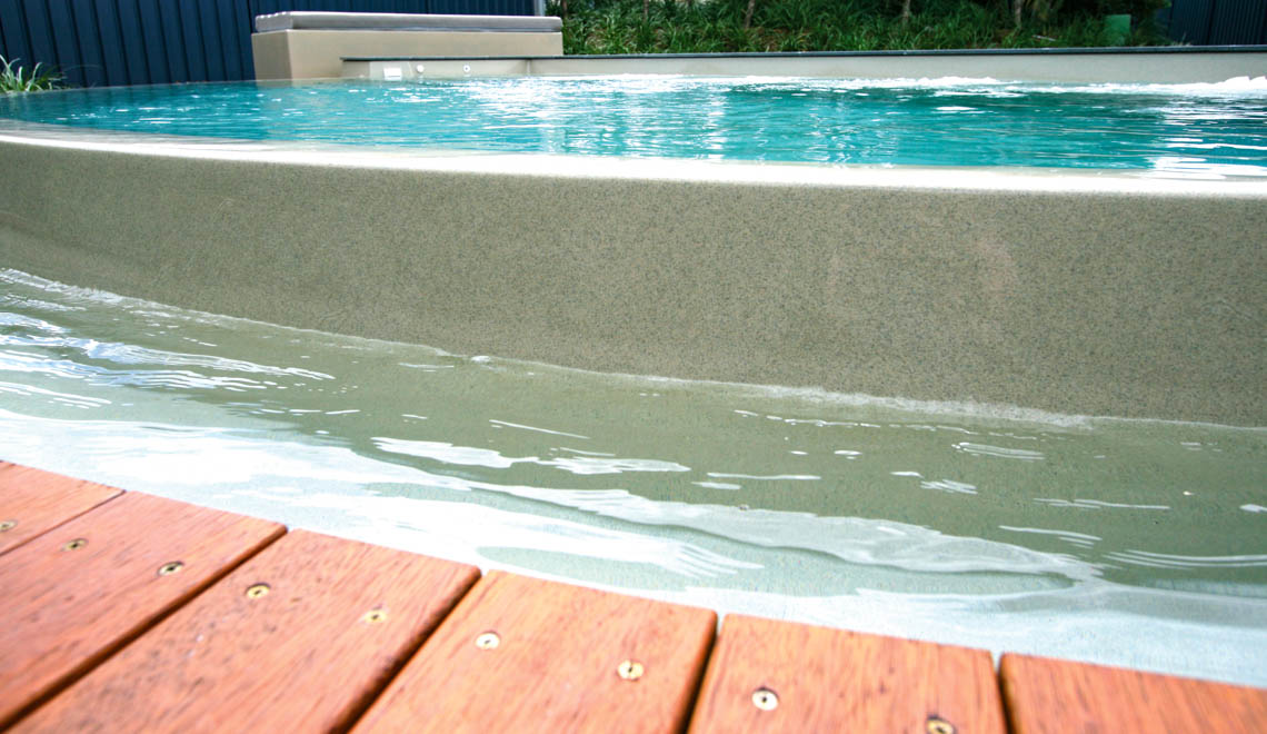 Leisure Pools Horizon disappearing edge swimming pool with built-in bench