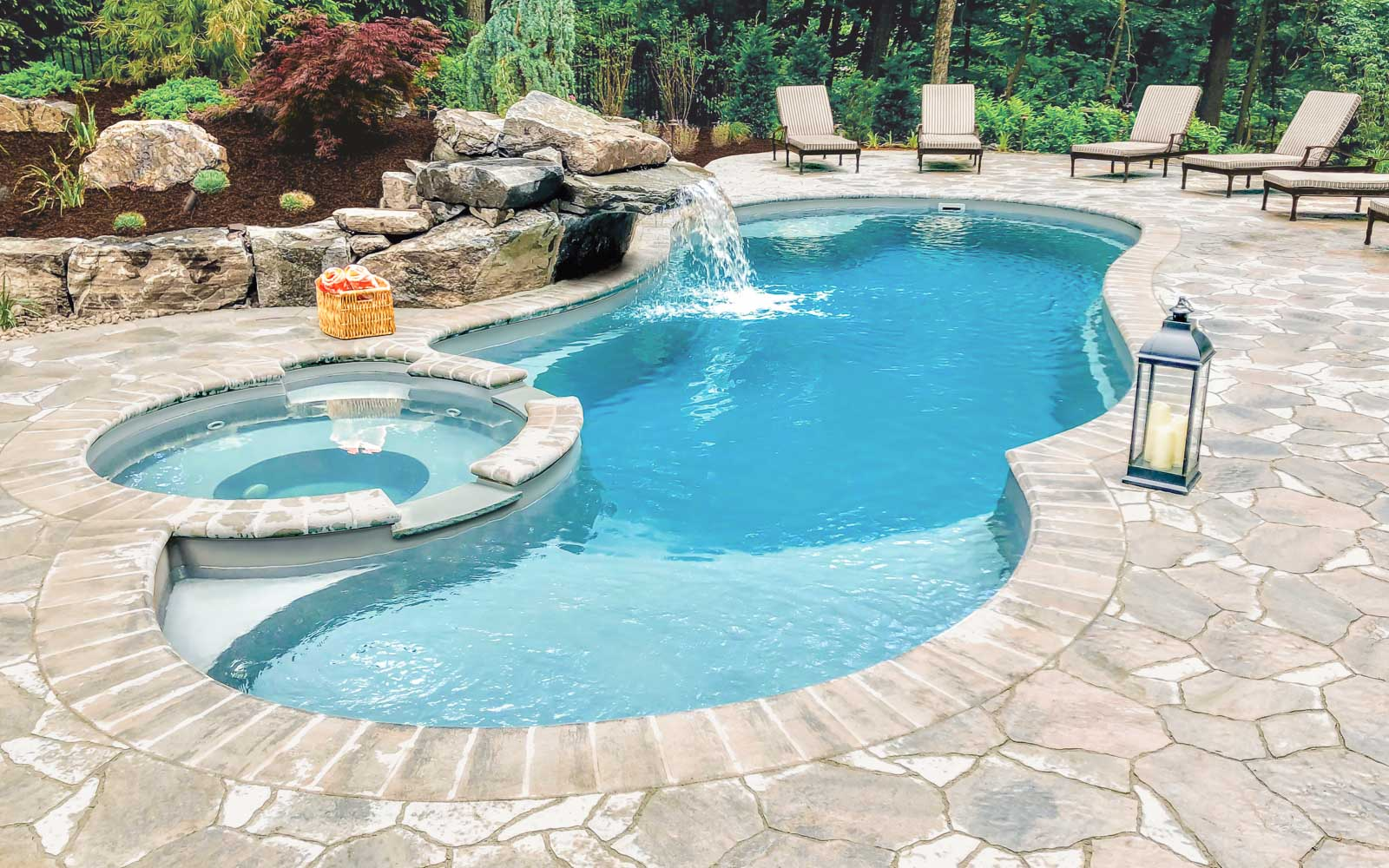 Leisure Pools Allure freeform fiberglass swimming pool with built-in spa and splash deck