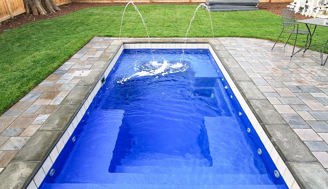Leisure Pools Palladium Plunge fiberglass swimming pool with wrapped bench area